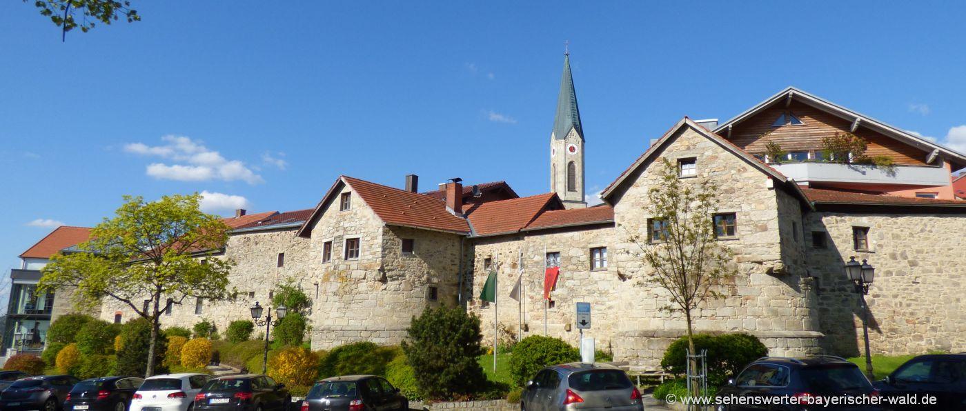 historische Stadtmauer in Waldkirchen mit Kirchturm im Hintergrund